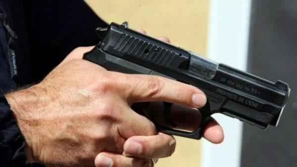 شرطي يشهر سلاحه الوظيفي